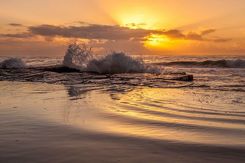 ola chocando contra un roca creando energías renovables