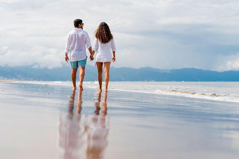 pareja pasea por la playa mejorando su salud psicológica