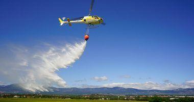 un helicóptero vierte agua para la extinción de incendios forestales