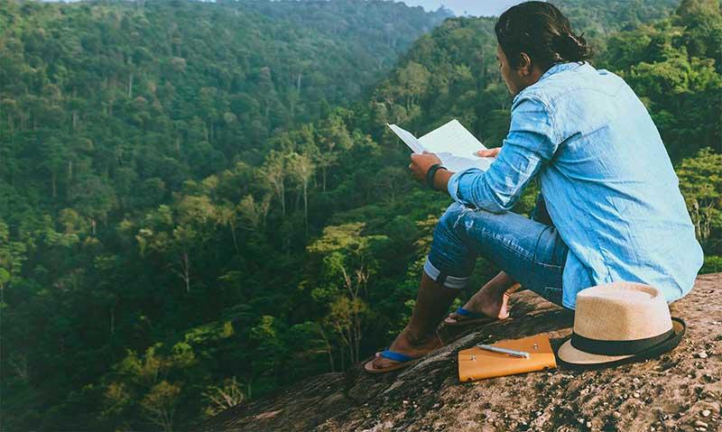 hombre lee sobre el cuidado del medio ambiente en el monte