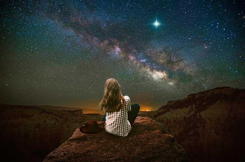 chica joven mira una lluvia de estrellas en agosto