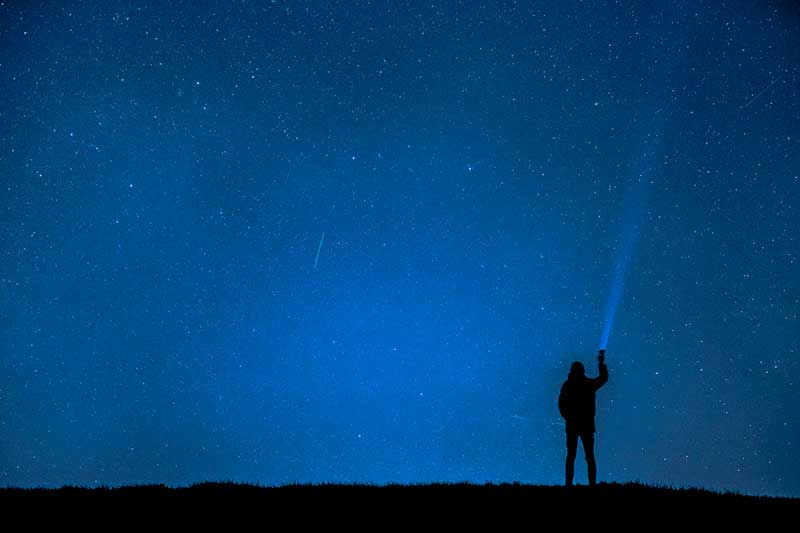 hombre observando una lluvia de estrellas