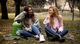 dos chicas conversan en un parque junto a un miniglú de Ecovidrio